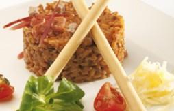 Cremiger Reis mit Serrano Serrano Schinken und Botifarró, serviert mit Quely Palitos mit Olivenöl